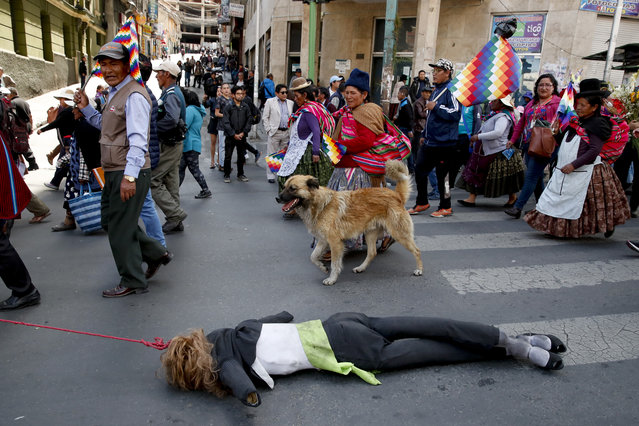 Anti-government demonstrators drag a dummy representing Bolivia's interim President Jeanine Anez in La Paz, Bolivia, Thursday, November 21, 2019. Anez sent a bill on holding new elections to congress Wednesday amid escalating violence that has claimed at least 30 lives since a disputed Oct. 20 vote and the subsequent resignation and exile of former President Evo Morales. (Photo by Natacha Pisarenko/AP Photo)