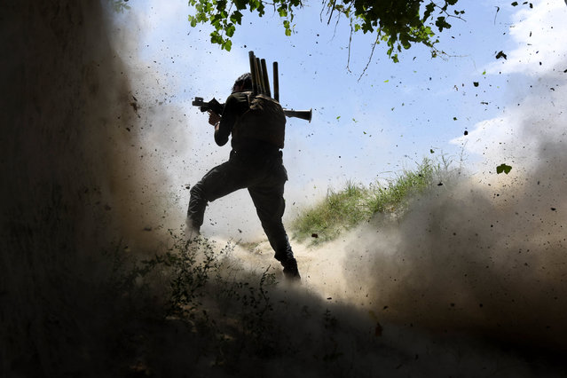 Afghan Army soldier uses his weapon among smoke and rubble after an attack by IS militants in Chapahar district of Nangarhar district, Afghanistan, 21 May 2017. Nangarhar, bordering Pakistan, is one of the most turbulent regions of Afghanistan and a stronghold of the Islamic State, as well as having a significant presence of the Taliban group. Since the end of NATO's combat mission in January 2015, insurgents have been gaining ground in various parts of Afghanistan and currently control, influence or are fighting the government in at least 43 percent of the territory, according to data from the United States. (Photo by Ghulamullah Habibi/EPA)