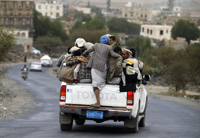 People ride on the back of a truck on a road linking Yemen's capital Sanaa with the northwestern city of Amran July 27, 2015. Fuel shortages in Yemen have caused hikes in taxi fees, forcing many to ride in overcrowded vehicles. (Photo by Khaled Abdullah/Reuters)