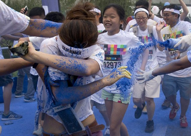 "A runner uses her arm to shield herself from color powder sprayed by volunteers as she and other participants run through a ""color station"" during a five-kilometer color run event in Beijing, China, Saturday, June 21, 2014. (Photo by Andy Wong/AP Photo)"
