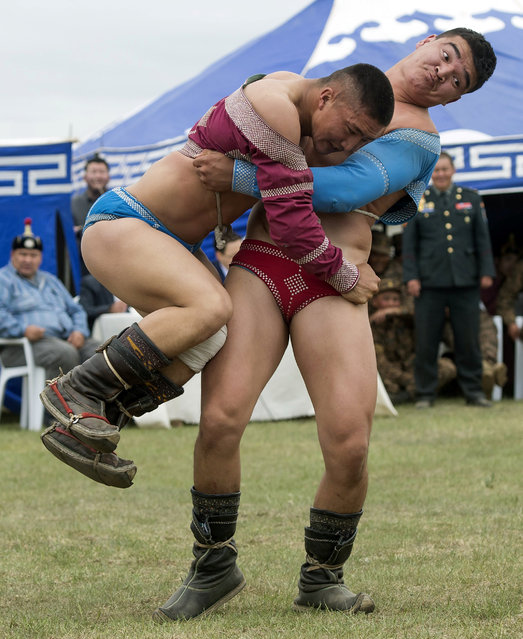 Mongolian wrestlers fight in a demonstration for US Secretary of State John Kerry as part of a Naadam ceremony, a competition which traditionally includes horse racing, Mongolian wrestling and archery, in Ulan Bator, Mongolia, June 5, 2016. (Photo by Saul Loeb/Reuters)