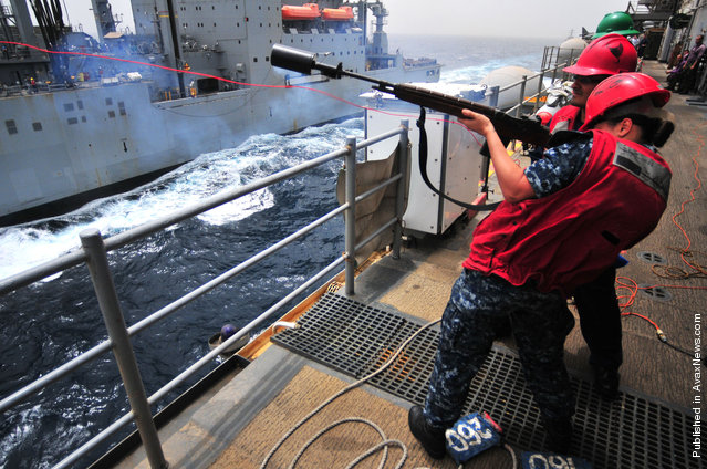 Gunner's Mate Seaman Megan Halliburton fires a shot line from the amphibious assault ship USS Boxer (LHD 4) to the Military Sealift Command dry cargo and ammunition ship USNS Alan Shepard (T-AKE 3) during a replenishment at sea