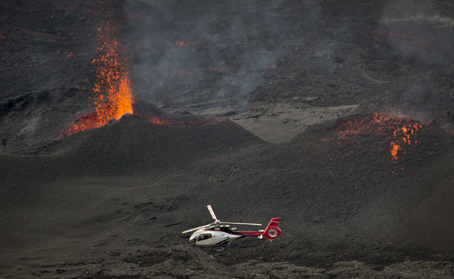 "A helicopter flies past as lava erupts from the Piton de la Fournaise ""Peak of the Furnace"" volcano, on the southeastern corner of the Indian Ocean island of Reunion Saturday, August 1, 2015. (Photo by Ben Curtis/AP Photo)"