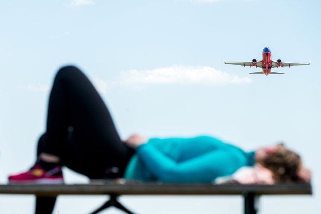 A plane takes off from Washington's Ronald Reagan National Airport as Julia Hurley of Washington relaxes on a picnic table at Gravelly Point Park in Arlington, Va., Wednesday, June 8, 2016, after bicycling to Mt. Vernon and back. (Photo by Andrew Harnik/AP Photo)