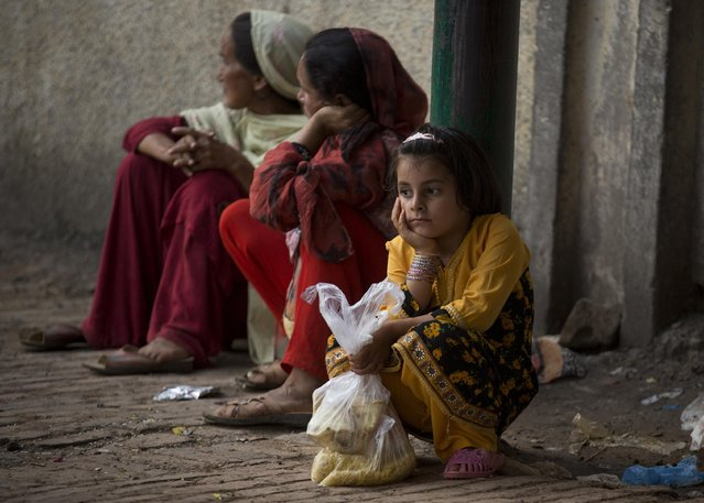 A Pakistani family waits for more food donations at a distribution center at a local shrine in Islamabad, Pakistan, Thursday, July 23, 2015. People who visit shrines and pray that their wishes are fulfilled would also offer food sometimes, to be distributed to the poor. Hundreds of poor families receive free food daily at the shrine. (Photo by B. K. Bangash/AP Photo)