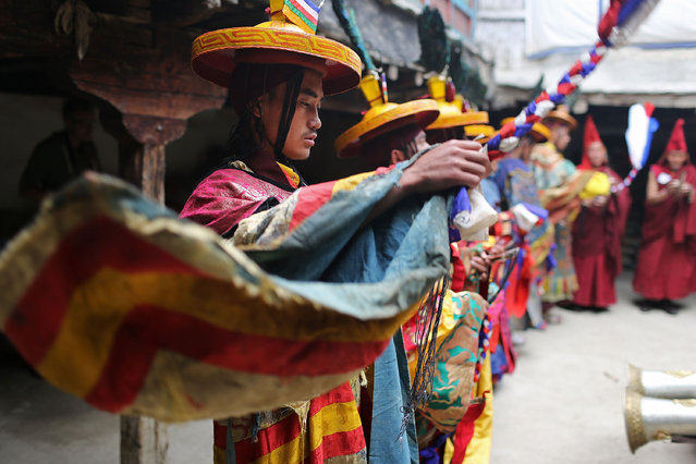Monks perform a ceremony in the former King's palace during the Tenchi Festival on May 25, 2014 in Lo Manthang, Nepal. The Tenchi Festival takes place annually in Lo Manthang, the capital of Upper Mustang and the former Tibetan Kingdom of Lo. Each spring, monks perform ceremonies, rites, and dances during the Tenchi Festival to dispel evils and demons from the former kingdom. (Photo by Taylor Weidman/Getty Images)