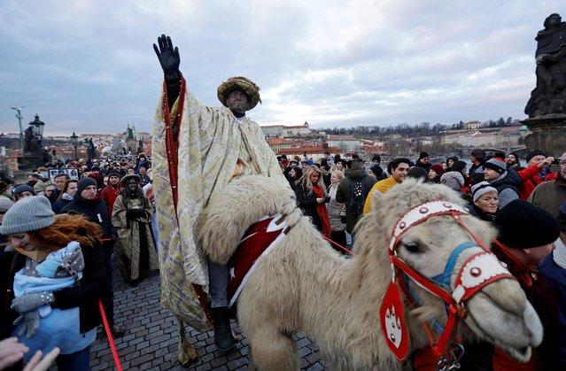 Men dressed as the Three Kings greet spectators as they ride camels during the Three Kings procession across the medieval Charles Bridge marking the beginning of Epiphany, in Prague, Czech Republic on January 5, 2020. (Photo by David W. Cerny/Reuters)