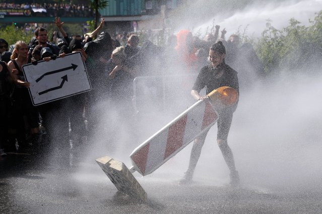 Riot police use water cannon against a protester throwning road signs on July 7, 2017 in Hamburg, northern Germany, where leaders of the world's top economies gather for a G20 summit. Protesters clashed with police and torched patrol cars in fresh violence ahead of the G20 summit, police said. German police and protestors had clashed already the day before at an anti-G20 march, with police using water cannon and tear gas to clear a hardcore of masked anti-capitalist demonstrators, AFP reporters said. (Photo by Odd Andersen/AFP Photo)