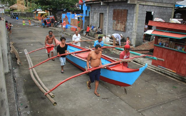 Residents carry to safety a wooden boat in Legaspi City, Albay province, south of Manila on December 2, 2019, as they prepare for Typhoon Kammuri. The Philippines was braced for powerful Typhoon Kammuri as the storm churned closer, forcing evacuations and threatening plans for the Southeast Asian Games events near the capital Manila. (Photo by Razvale Sayat/AFP Photo)