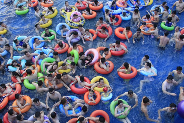 "Chinese holidaymakers crowd a swimming pool at a water park in Nanchang city, east China's Jiangxi province, 16 July 2017. Days of heat wave drove many citizens to the water park for fun and coolness. Nanchang has become the new four ""furnace cities"" in China according to a ranking of the hottest cities released by the China Meteorological Administration on July 9. (Photo by Imaginechina/Rex Features/Shutterstock)"
