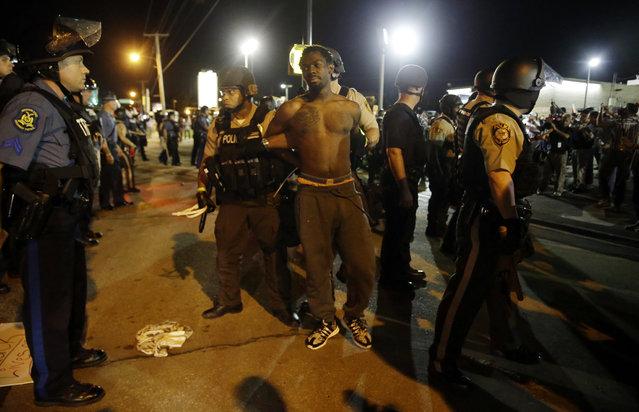 St. Louis County Police make an arrest along West Florissant Avenue, Monday, August 10, 2015, in Ferguson, Mo. (Photo by Jeff Roberson/AP Photo)