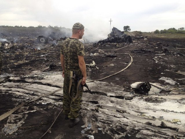 An armed pro-Russian separatist stands at a site of a Malaysia Airlines Boeing 777 plane crash in the settlement of Grabovo in the Donetsk region, July 17, 2014. The Malaysian airliner MH-17 was shot down over eastern Ukraine by pro-Russian militants on Thursday, killing all 295 people aboard, a Ukrainian interior ministry official said. (Photo by Maxim Zmeyev/Reuters)