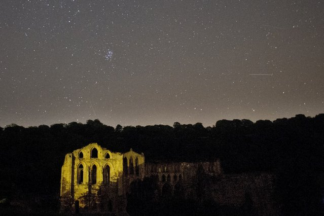 A meteor passes across the sky above Rievaulx Abbey during the peak in activity of the annual Perseids meteor shower in the village of Rievaulx, near Helmsley, northern England on August 13, 2015. (Photo by Oli Scarff/AFP Photo)