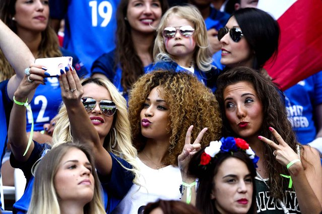 Ludivine Payet, left, wife of France's Dimitri Payet, poses for a photo with others on the stands during the Euro 2016 round of 16 soccer match between France and Ireland, at the Grand Stade in Decines-Charpieu, near Lyon, France, Sunday, June 26, 2016. (Photo by Thanassis Stavrakis/AP Photo)