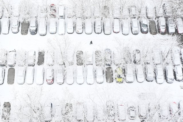 This aerial view shows a pedestrian walking across a parking lot in a residential area after snow fell in Beijing on January 6, 2020. (Photo by Wang Zhao/AFP Photo)