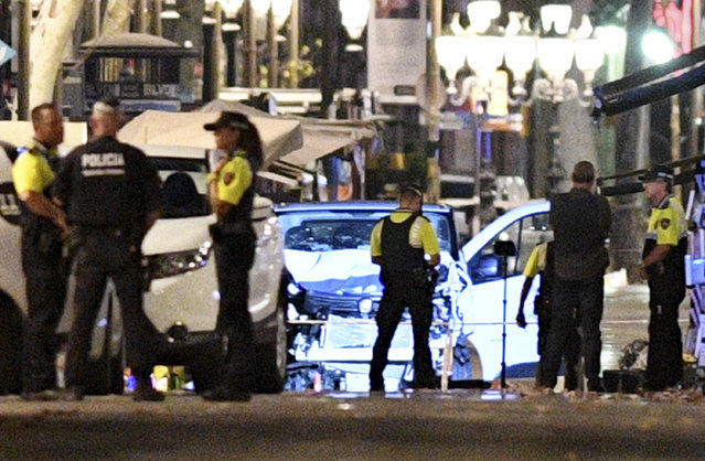 A damaged van, believed to be the one used in the attack, is surrounded by police officers in the Las Ramblas area on August 17, 2017 in Barcelona, Spain. Officials say 13 people are confirmed dead and at least 50 injured after a van plowed into people in the Las Ramblas area of the city. (Photo by David Ramos/Getty Images)