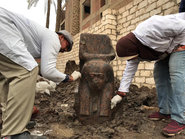 In this Wednesday, December 11, 2019, photo released by Egyptian Ministry of Antiquities, archaeology workers clean a small pink granite statue of Ramses II, near the ancient pyramids of Giza, Egypt. Archeologists in Egypt unveiled two new discoveries, the rare statue of Ramses II, one of the country's most famous pharaohs, and a diminutive ancient sphinx that was found in the southern desert province of Minya. (Photo by Egyptian Ministry of Antiquities via AP Photo)