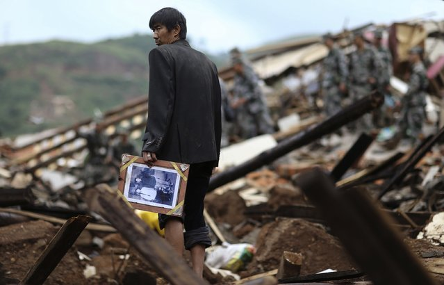A man holds a picture as he stands among debris of collapsed buildings after an earthquake hit Longtoushan township of Ludian county, Yunnan province August 4, 2014. A magnitude 6.3 earthquake struck southwestern China on Sunday, killing at least 398 people in a remote area of Yunnan province, and causing thousands of buildings, including a school, to collapse. (Photo by Wong Campion/Reuters)