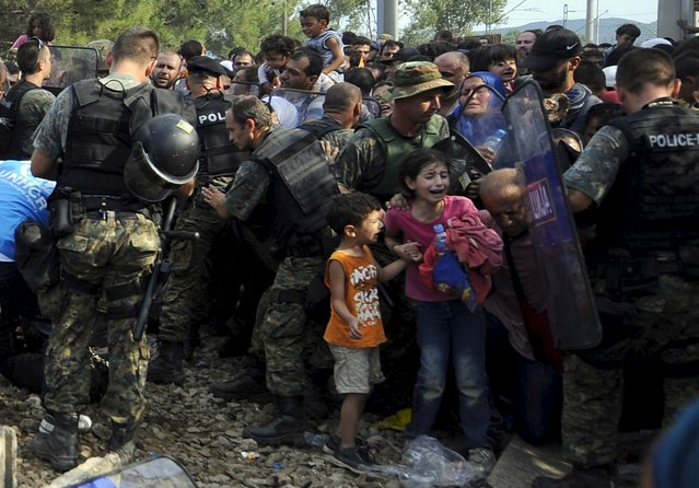 People react as they are held back by police at the border line dividing Macedonia and Greece August 21, 2015. (Photo by Ognen Teofilovski/Reuters)