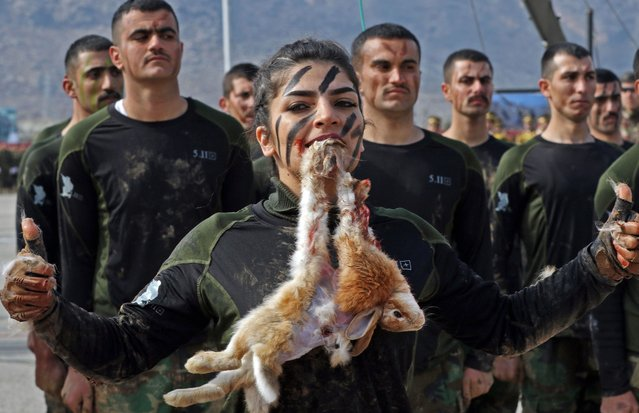 An Iraqi Kurdish Peshmerga female officer bites a Rabbit while demonstrating skills during a graduation ceremony in the Kurdish town of Soran, about 100 kilometres northeast of the capital of Iraq's autonomous Kurdish region Arbil, on February 12, 2020. (Photo by Safin Hamed/AFP Photo)