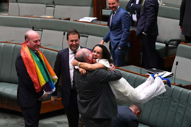 Liberal MP Warren Entsch lifts up Labor MP Linda Burney as they celebrate the passing of the Marriage Amendment Bill in the House of Representatives at Parliament House in Canberra, Thursday, December 7, 2017. (Photo by Lukas Coch/AAP Image)