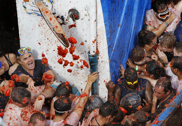 """Crowds of people throw tomatoes at each other, during the annual """"Tomatina"""" tomato fiesta, in the village of Bunol, 50 kilometers from Valencia, Spain, Wednesday, August 26, 2015. (Photo by Alberto Saiz/AP Phot)"""