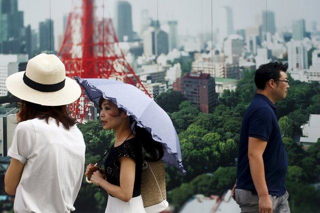 People walk past a photograph showing the Tokyo Tower in the Ginza shopping districts in Tokyo, August 3, 2015. (Photo by Thomas Peter/Reuters)