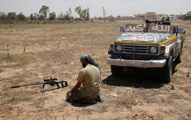 A fighter of Libyan forces allied with the U.N.-backed government prays in front of his sniper rifle during a battle with Islamic States fighters in Sirte, Libya, July 21, 2016. (Photo by Goran Tomasevic/Reuters)