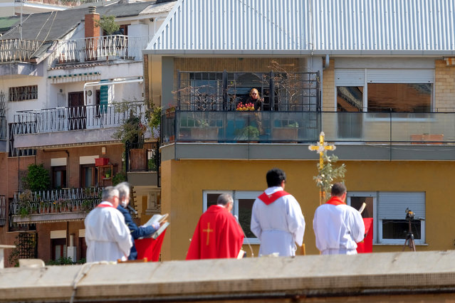 A faithful from a facing balcony follows the celebration of the Palm Sunday mass on the roof of the church of San Pio X, in Rome, Sunday, April 5, 2020. Churches are closed to faithful all over Italy due to the coronavirus outbreak. The new coronavirus causes mild or moderate symptoms for most people, but for some, especially older adults and people with existing health problems, it can cause more severe illness or death. (Photo by Mauro Scrobogna/LaPresse via AP Photo)