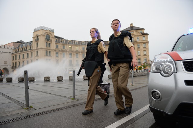 Police officers in protective gear woperate at Karlsplatz (Stachus) square after a shooting in the Olympia shopping centre was reported in Munich, southern Germany, Friday, July 22, 2016. (Photo by Andreas Gebert/DPA via AP Photo)