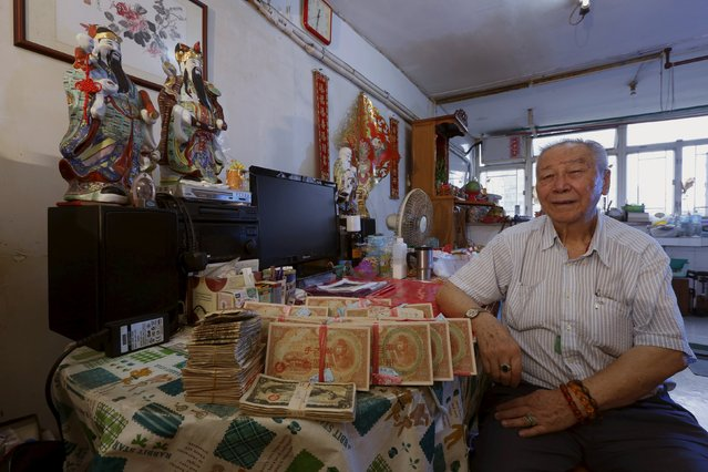 Lam Yin-bun, 89, poses with his Japanese military yen of around 110,000, left by his father, at his public housing home in Hong Kong, China June 25, 2015. On August 14, 2015, a group of World War Two survivors in Hong Kong, including Lam, took their 70-year-old fight and demanded Tokyo to convert millions of Japanese military yen issued during the war into usable money. Japan occupied Hong Kong for three years and eight months, during which people were forced to exchang. (Photo by Bobby Yip/Reuters)