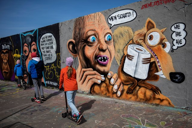 """A graffiti showing Gollum from """"Lord of the Rings"""", watching squirrel Scrat from """"Ice Age"""" stealing a roll of toilet paper during the coronavirus crisis on April 15, 2020 in Berlin, Germany. As the rate of new infections nationwide continues to slow, the German government is seeking to establish and implement a roadmap for easing restrictions on public life and the burden the virus is having on the economy. So far over there are over 130,000 cases of confirmed infection of coronavirus in Germany, over 3,000 people have died and over 57,000 people have recovered. (Photo by Maja Hitij/Getty Images)"""