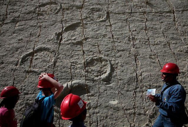 Visitors look at dinosaur footprints while visiting with a tour guide the Cal Orcko cliff in Cal Orcko, on the outskirts of Sucre, Bolivia, July 22, 2016. (Photo by David Mercado/Reuters)