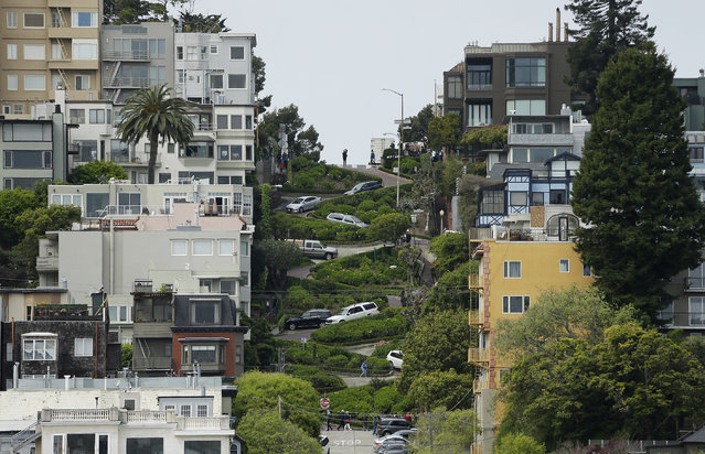 Cars wind their way down Lombard Street in San Francisco, Monday, April 15, 2019. Thousands of tourists may soon have to pay as much as $10 to drive down the world-famous crooked street if a proposal to establish a toll and reservation system becomes law. In the summer months, an estimated 6,000 people a day visit the 600-foot-long street, creating lines of cars that stretch for blocks. (Photo by Eric Risberg/AP Photo)
