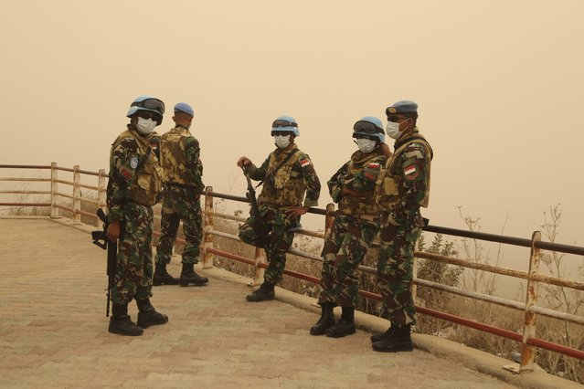 U.N peacekeepers of the United Nations Interim Force in Lebanon (UNIFIL) wear face masks while they monitor the Lebanese-Israeli border during a sandstorm in Kfar Kila village, in south Lebanon September 8, 2015. (Photo by Aziz Taher/Reuters)