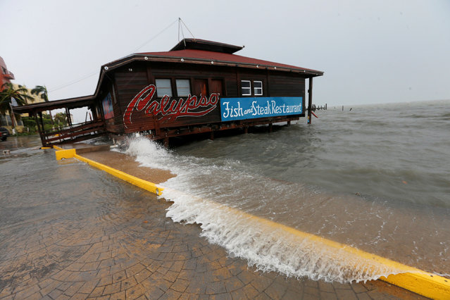 A large wave splashes onto a restaurant along the beach, after Hurricane Earl hits, in Belize City, Belize August 4, 2016. (Photo by Henry Romero/Reuters)