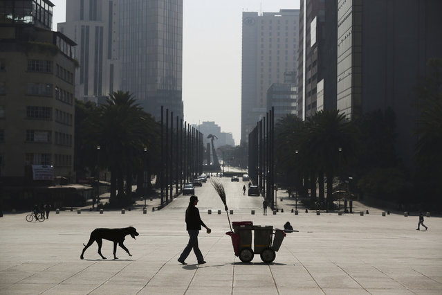 """A woman walks her dog past a trash worker's cart, amid an empty plaza at Revolution Monument in Mexico City, Wednesday, April 1, 2020. Mexico's government has broadened its shutdown of """"non essential activities"""", and prohibited gatherings of more than 50 people as a way to help slow down the spread of COVID-19. The one-month emergency measures will be in effect from March 30 to April 30. (Photo by Fernando Llano/AP Photo)"""