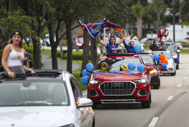 Students participate in a parade of vehicles celebrating the area's graduating 2020 High School seniors on May 14, 2020 in Aventura, Florida. The graduating seniors were cheered on as they drove through the city escorted by the Aventura Police Department, students and parents. The  unorthodox graduation ceremony was created as a way to safely celebrate during the coronavirus pandemic. (Photo by Joe Raedle/Getty Images)