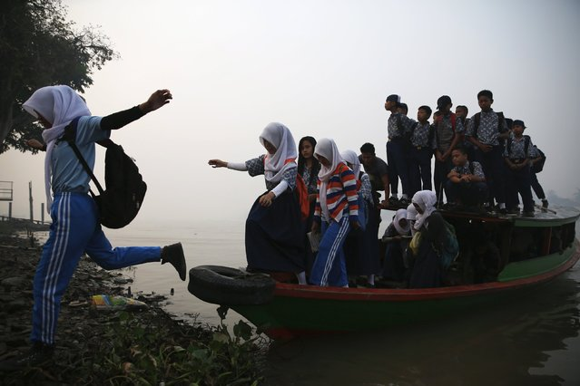 Students jump from a wooden boat as haze blankets the Musi River while they travel to school in Palembang, on Indonesia's Sumatra island, September 10, 2015. (Photo by Reuters/Beawiharta)