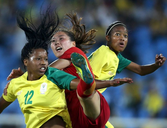 Li Yang (C) of China vies for the ball with Jermaine Seoposenwe (L) and Linda Motlhalo (R) of South Africa during the women's preliminary round match between South Africa and China for the Rio 2016 Olympic Games Soccer tournament at the Olympic Stadium in Rio de Janeiro, Brazil, 06 August 2016. (Photo by Orestis Panagiotou/EPA)