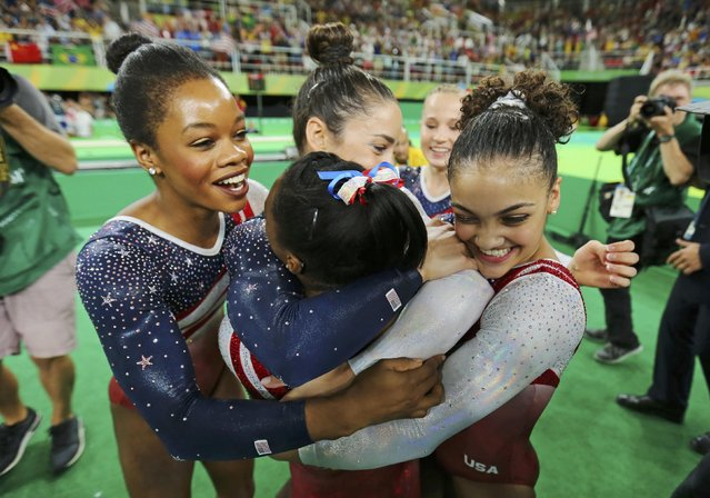 2016 Rio Olympics, Artistic Gymnastics, Final, Women's Team Final, Rio Olympic Arena, Rio de Janeiro, Brazil on August 9, 2016. Simone Biles (USA) of USA (back-facing camera) is hugged by team mates (from L) Gabrielle Douglas (USA) of USA (Gabby Douglas), Alexandra Raisman (USA) of USA (Aly Raisman), Madison Kocian (USA) of USA and Laurie Hernandez (USA) of USA following her floor routine during the women's team final. Team USA won gold in the event. (Photo by Mike Blake/Reuters)