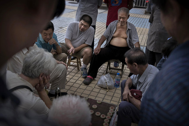 Chinese men play Mahjong, very popular local game, in the street on September 5, 2014 in Beijing, China. (Photo by Kevin Frayer/Getty Images)