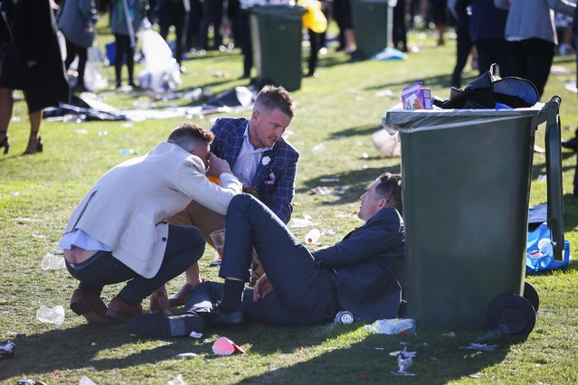 One lad flashes his crack as he lolls about with pals on the floor next to a wheelie bin on 2017 Derby Day at Flemington Racecourse on November 4, 2017 in Melbourne, Australia. (Photo by Splash News and Pictures)