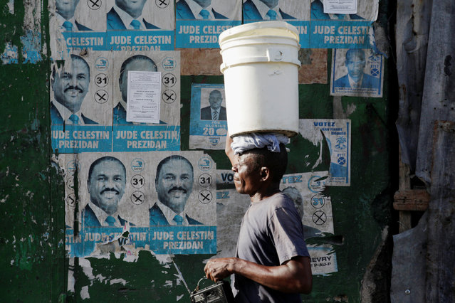 A man carrying a bucket on his head walks next to ripped electoral signs of presidential candidate Jude Celestin in a street of Port-au-Prince, Haiti, July 22, 2016. (Photo by Andres Martinez Casares/Reuters)