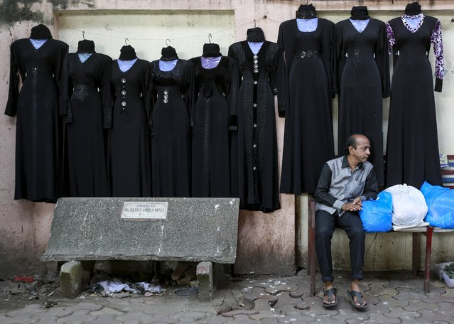 A vendor waits for customers as burqas on sale are displayed on a wall at a market in Mumbai, India, September 8, 2015. (Photo by Danish Siddiqui/Reuters)