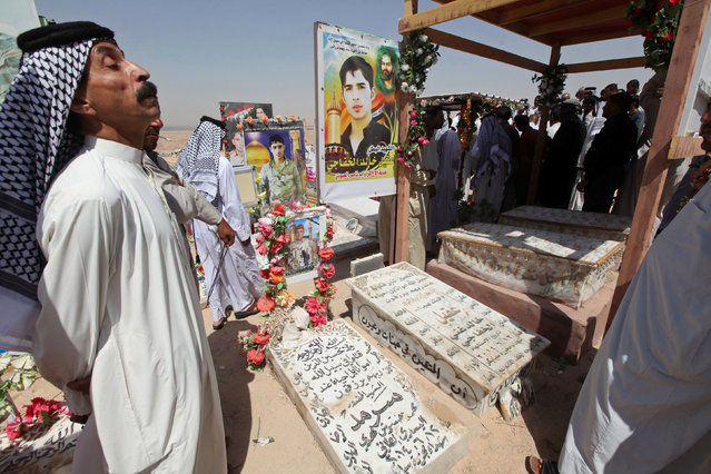 """Residents visit the graves of their relatives at the Wadi al-Salam cemetery, Arabic for """"Peace Valley"""", in Najaf, south of Baghdad, Iraq July 27, 2016. (Photo by Alaa Al-Marjani/Reuters)"""