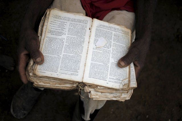 Nene Charles reads a bible in Creole at a refugee camp for Haitians returning from the Dominican Republic on the outskirts of Anse-a-Pitres, Haiti, September 6, 2015. (Photo by Andres Martinez Casares/Reuters)