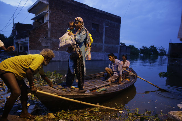 People leave for safer places due to the flooding in the river Ganges in Allahabad, India, Tuesday, August 23, 2016. Days of heavy rain have caused the Ganges River and its tributaries to rise above the danger level during the past 48 hours in about 20 districts of the states of Madhya Pradesh, Bihar and Uttar Pradesh. (Photo by Rajesh Kumar Singh/AP Photo)