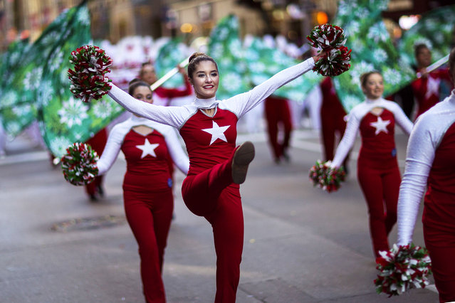 Cheerleaders march along Sixth Avenue during the Macy's Thanksgiving Day Parade in New York, Thursday, November 23, 2017. (Photo by Andres Kudacki/AP Photo)