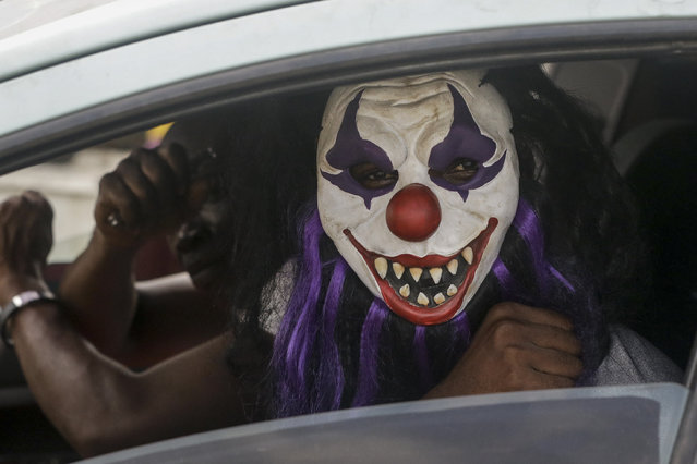 A passenger sits in a car wearing a mask, which he said was to prevent him catching the new coronavirus, in Lagos, Nigeria Friday, March 27, 2020. (Photo by Sunday Alamba/AP Photo)